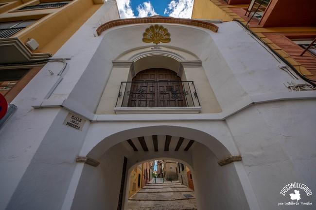Pequeño templo encalado con arco de acceso a la vía de detrás