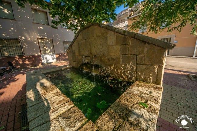 Se trata de una elegante fuente de piedra con frontón triangular