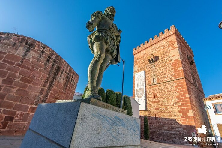 Estatua de Miguel de Cervantes con el cubillo y torreón de fondo